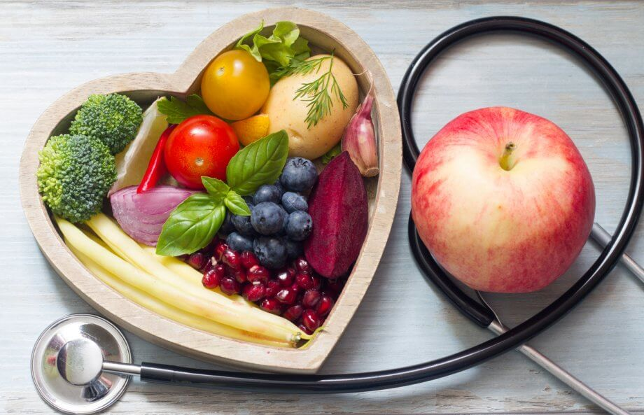 A photograph of fruits and vegetables in a heart shaped bowl. Wrapped around the bowl is a stethoscope and an apple.