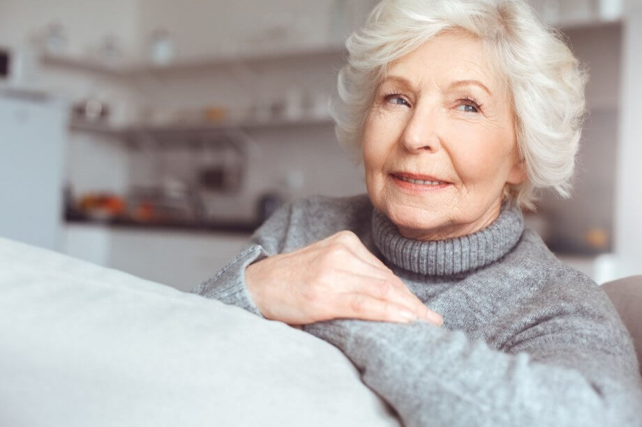 An older woman with short wavy white hair sitting in a home setting thinking about something while looking off to the side.