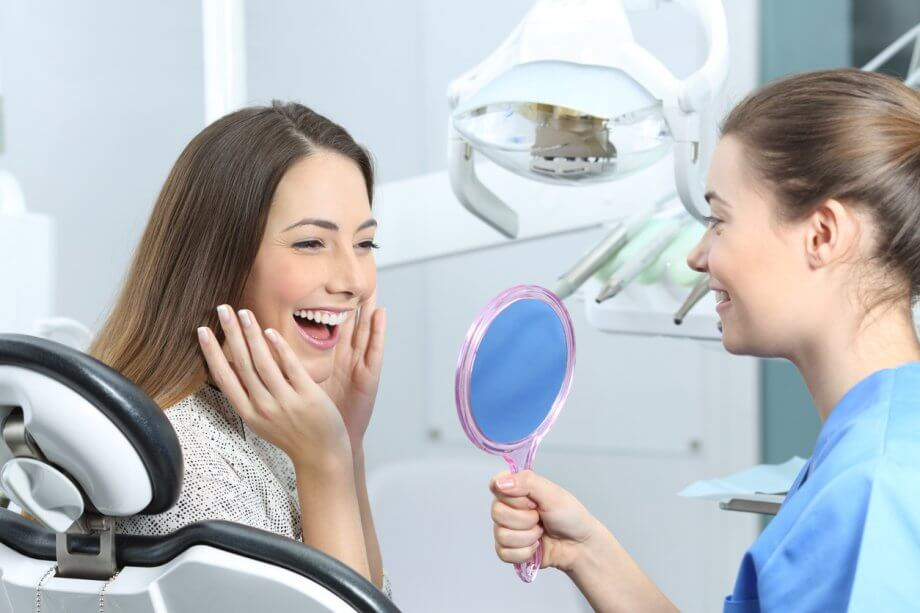 A woman with long straight brown hair smiling widely as a dentist holds up a mirror to her face in a dentists office.
