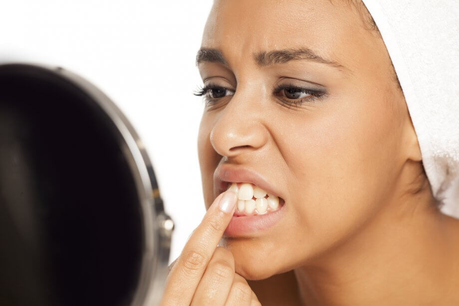 Photograph of a young woman looking at her teeth in the mirror unhappily while rubbing them with her finger.
