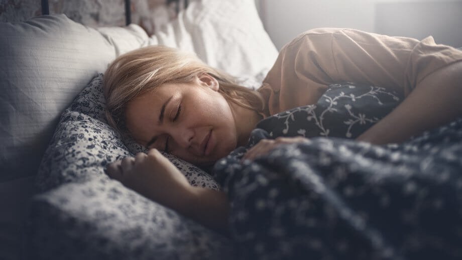 Woman with blonde hair sleeping under blankets in bed.