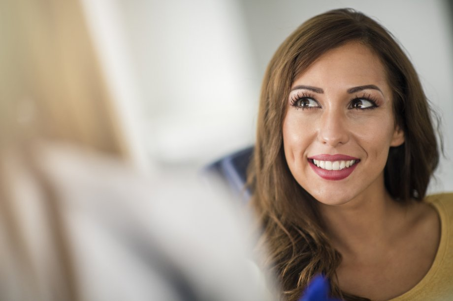Woman with Long Brown Hair Looking Up in an Office Setting and Smiling
