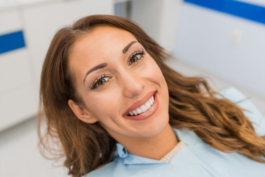 Young woman with light brown hair smiling while being seen by a dentist.